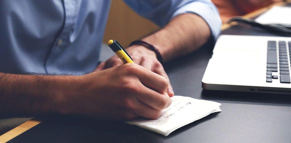 Photo d'un homme qui écrit sur du papier avec un ordinateur sur la table